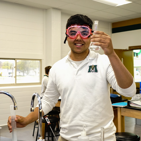 A high school student uses chemistry equipment.