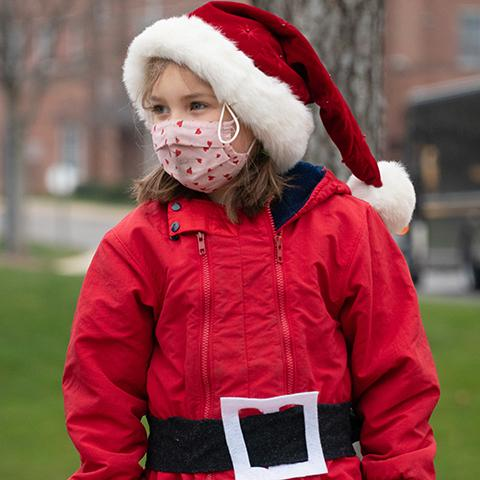 A St. Stephen student sings Christmas carols while dressed as Santa Claus.