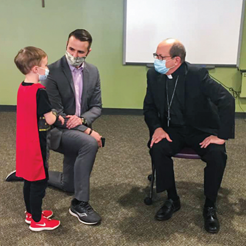 Bishop Walkowiak speaks with Saint Thomas the Apostle's assistant principal and a student.